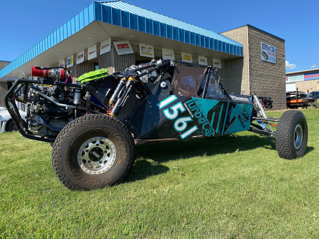 Image of a black and turquoise TurboLab Offroad Vehicle on green lawn
